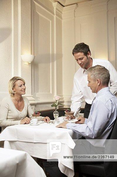 Kellner bedient Ehepaar mittleren Alters im Restaurant