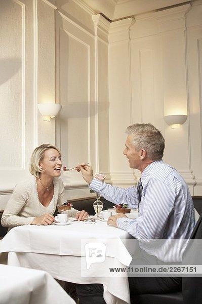 Mann füttert Frau mit Dessert in einem Restaurant