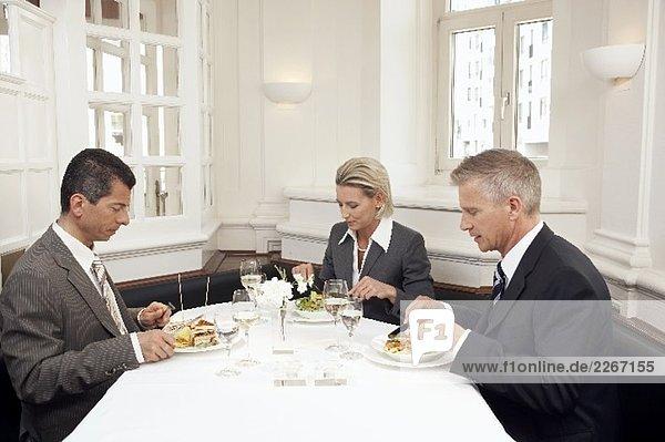 Frau mit zwei Männern bei einem Geschäftsessen