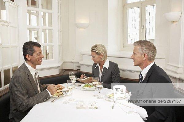Frau zwischen zwei Männer bei einem Geschäftsessen