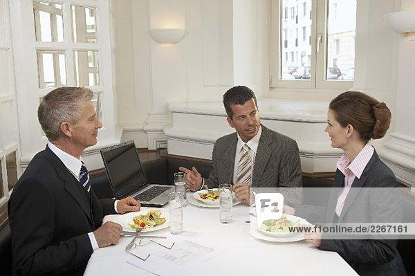Zwei Männer sitzen mit Geschäftsfrau beim Essen