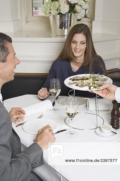 Kellner serviert Frau und Mann frische Austern im Restaurant