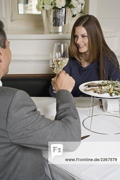 Paar stösst mit Weissweingläsern an im Restaurant