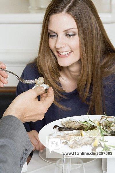 Mann reicht Frau frische Auster im Restaurant