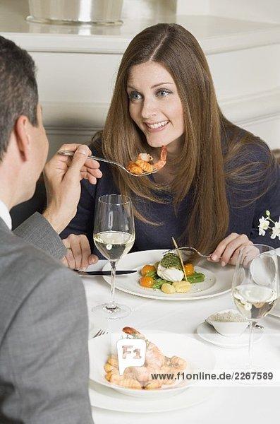 Mann reicht Frau Gabel mit Garnele im Restaurant