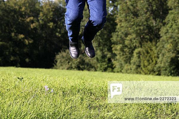 ein Mann mit Jeans springt auf einer Sommerwiese in die Höhe