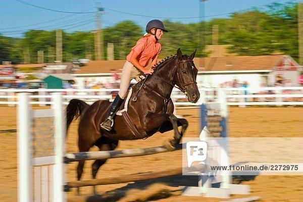 Teen Girl  Wettbewerb trägt einen Helm und Reiten Kleidung  ein Pferd springen im Wettbewerb in einen Korral auf einer Messe.