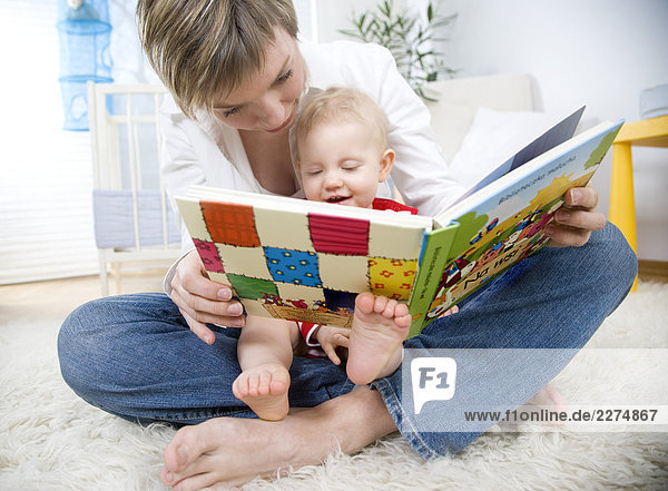 baby girl and mum reading a book