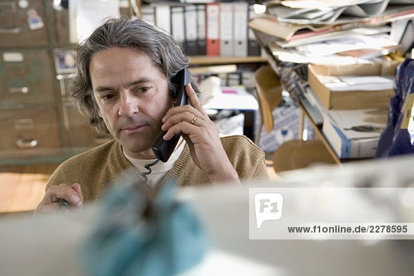 A man on the phone in his office