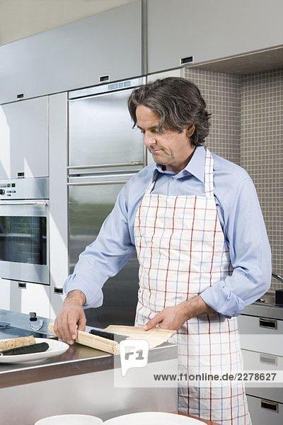Ein reifer Mann  der Sushi in der Küche zubereitet.