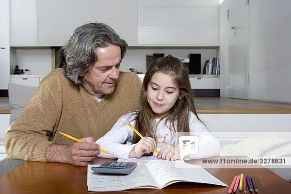 Ein Vater hilft seiner Tochter bei den Hausaufgaben.