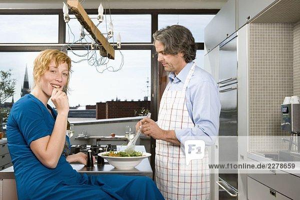 Ein Mann  der eine Mahlzeit in der Küche zubereitet  mit einer Frau  die in der Nähe sitzt.
