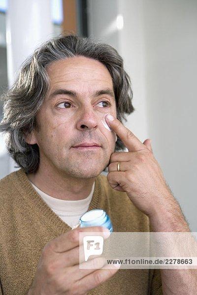 Ein reifer Mann  der Feuchtigkeitscreme auf sein Gesicht aufträgt.