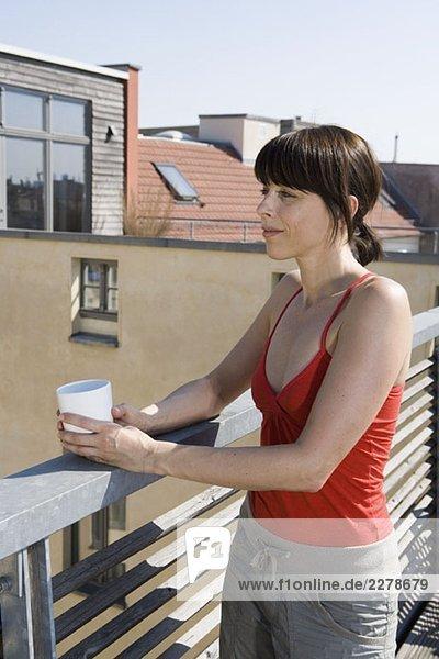 Eine Frau  die auf einer Dachterrasse mit einer Tasse steht. Eine Frau, die auf einer Dachterrasse mit einer Tasse steht.