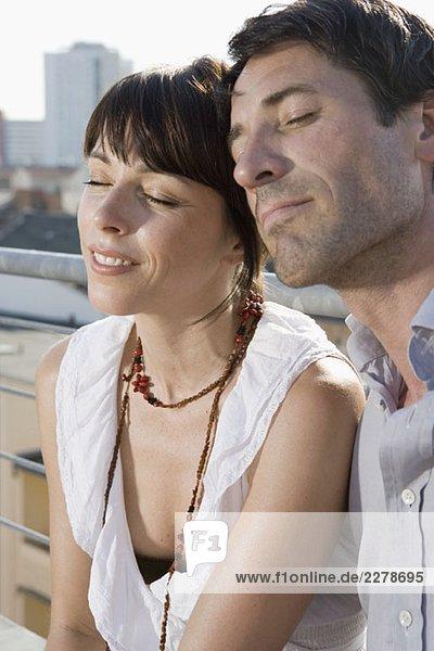 Ein Paar sitzt mit geschlossenen Augen auf einer Dachterrasse.