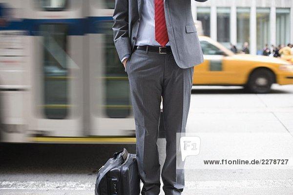 Ein Geschäftsmann  der auf einem Bürgersteig steht und ein Handy benutzt.