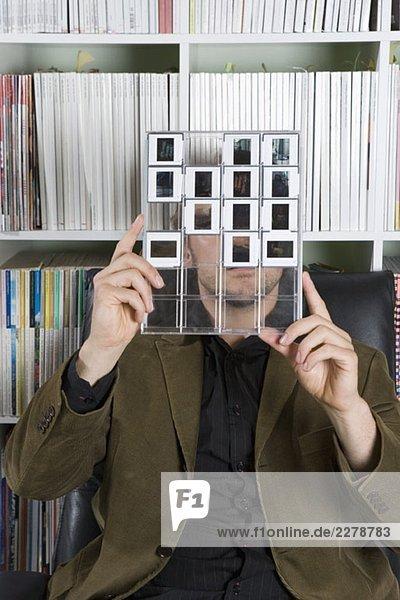 Ein Mann  der sich ein Kontaktblatt mit Dias ansieht.