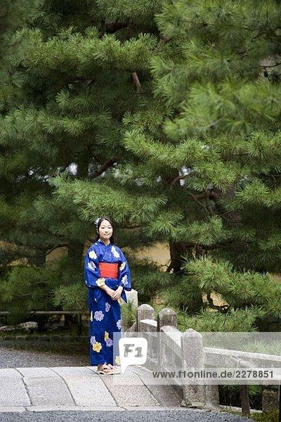 Eine Frau  die einen Kimono trägt  steht auf einer Brücke.