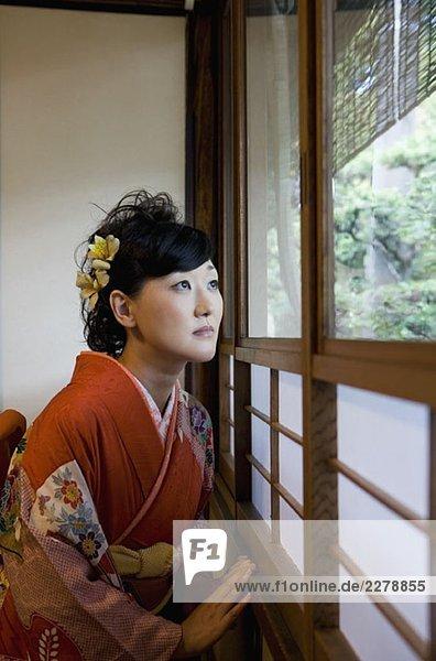 Eine Frau  die einen Kimono trägt und durch ein Fenster schaut.