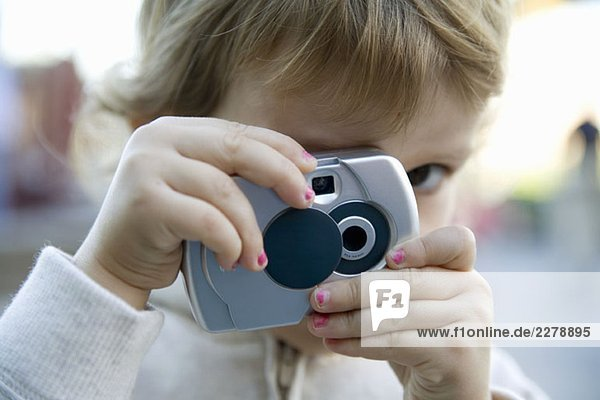 A young girl taking a photograph