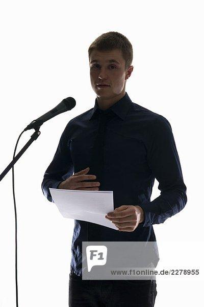 Ein junger Mann  der eine Rede in ein Mikrofon hält.