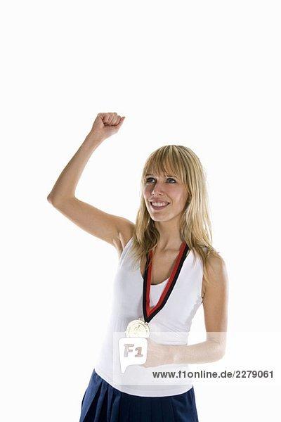 Eine Frau  die eine Goldmedaille hält und ihre Faust hebt.