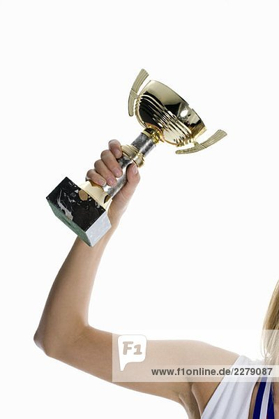 Der Arm einer Sportlerin hält eine Siegertrophäe hoch.