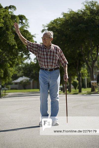 Ein älterer Mann  der auf der Straße geht und winkt.