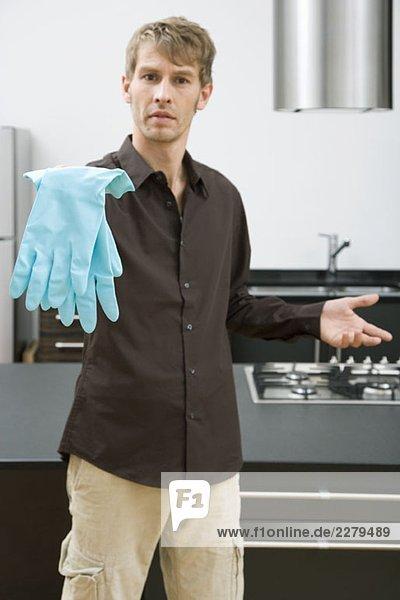 Ein Mann hält Waschhandschuhe in der Hand.