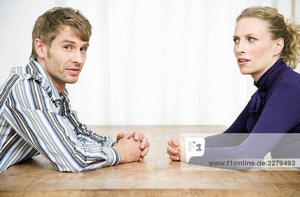 Ein Paar sitzt sich an einem Tisch gegenüber.