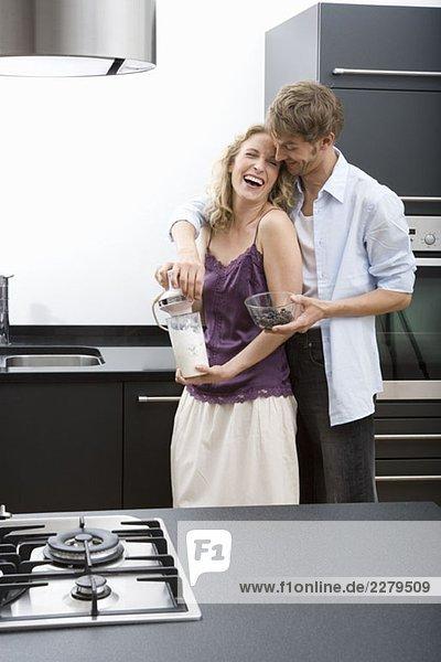 Ein erwachsener Mann mit den Armen um eine erwachsene Frau  die einen elektrischen Mixer hält.