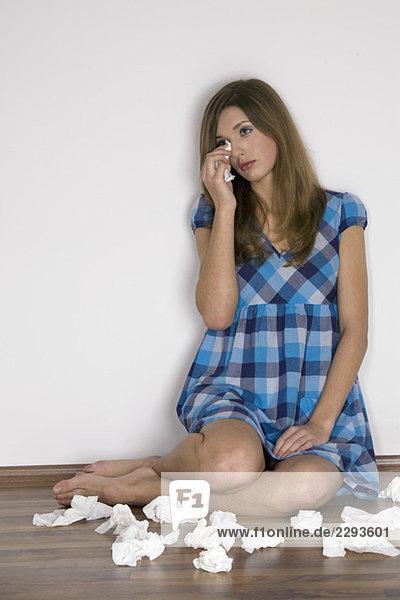 Junge Frau trocknet Tränen mit Taschentuch