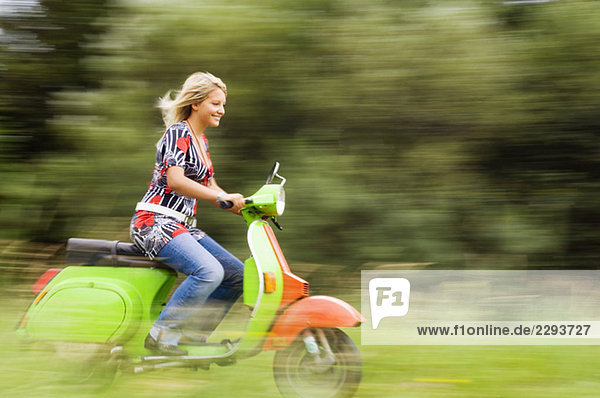 Young woman on scooter  wind blowing through hair