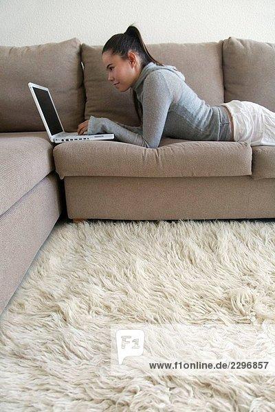 Teenagerin auf Sofa liegend mit laptop