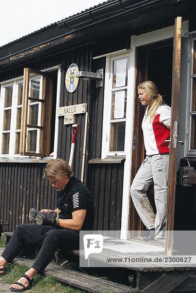Ein Mann Blick auf seinen Schuh-eine Frau in einem Hauseingang Schweden