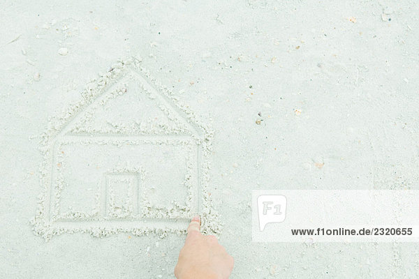 Hand drawing house in sand  cropped view