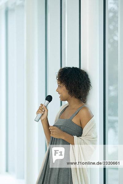 Junge Frau lehnt sich an die Stange  singt ins Mikrofon  schaut weg