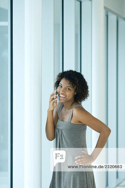 Junge Frau mit der Hand auf der Hüfte stehend  mit dem Handy  lächelnd vor der Kamera