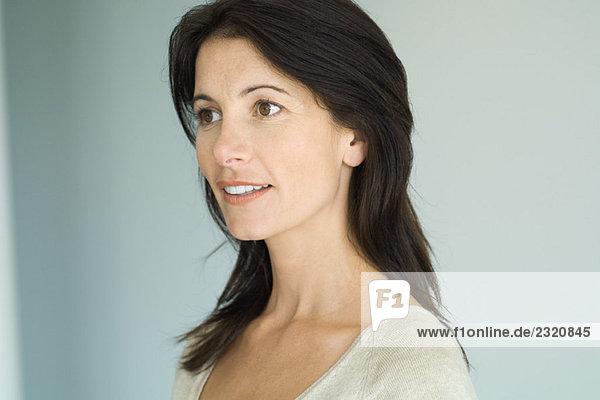 Brunette woman  smiling  looking away  head and shoulders  portrait