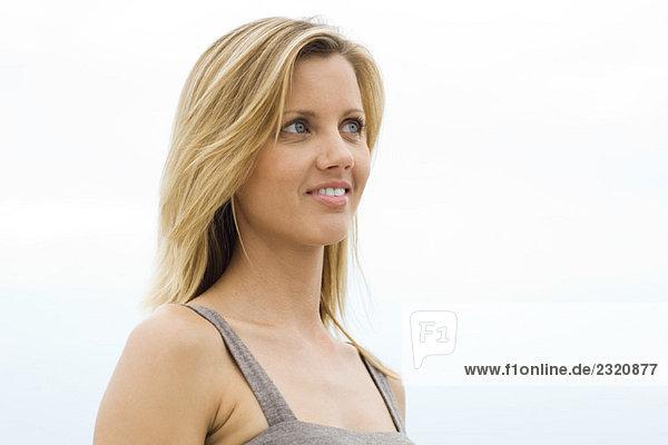 Blonde woman smiling  looking away  head and shoulders