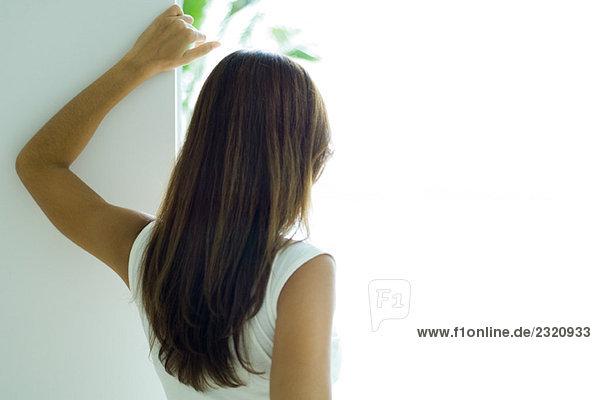 Frau schaut aus dem Fenster  Rückansicht  Nahaufnahme
