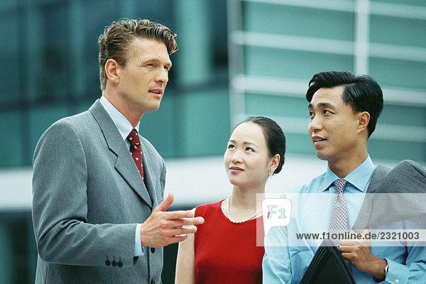 Drei Profis chatten im Freien  eine Geste mit der Hand
