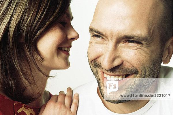 Frau flüstert dem Mann ins Ohr  beide lächelnd  Nahaufnahme