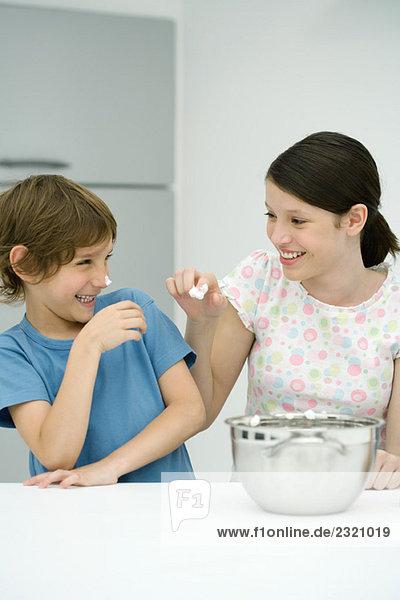 Bruder und Schwester stehen in der Küche  Mädchen setzt Schlagsahne auf die Nase des Jungen  beide lächelnd