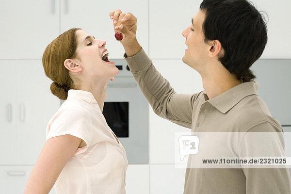 Paar steht zusammen in der Küche  Mann füttert Frau Kirschen  Seitenansicht