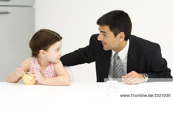 Vater und Tochter sitzen am Tisch und schauen sich an  das kleine Mädchen isst Müsli.