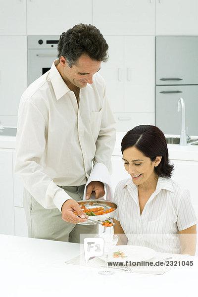 Mann steht neben dem Esstisch und serviert seiner Frau das Essen.