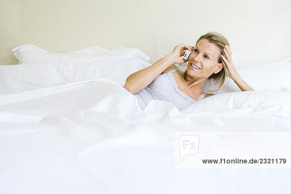 Frau im Bett liegend  mit dem Handy  lächelnd