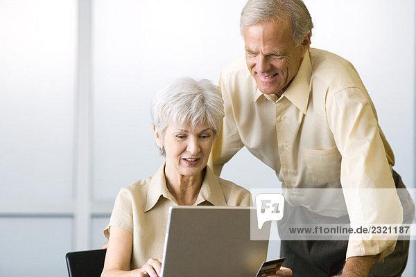 Reife Paare  die zusammen auf den Laptop schauen  lächelnd  Frau sitzend  Mann stehend