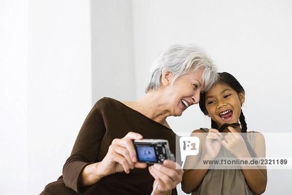 Seniorin fotografiert sich selbst und Tochter mit Digitalkamera  beide lachend